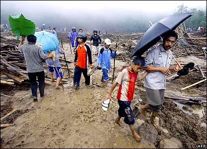 People walk along their levelled village in Sijeruk, some 370 kilometres (230 miles) east of the capital Jakarta, after a landslide devastated the area 04 January 2006.