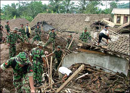 Indonesian soldiers and local residents stand in the wreckage of Sijeruk village in Banjarnegara district, Central Java, Indonesia Wednesday Jan. 4, 2006.
