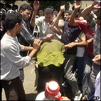 Pro-government supporters beat a member of the Kifaya movement in Cairo