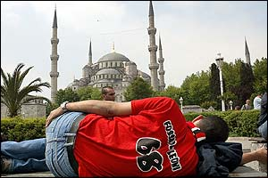 An AC Milan fan has a nap in the centre of Istanbul