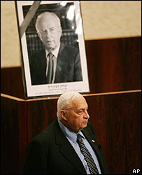 Ariel Sharon beneath a picture of Yitzhak Rabin