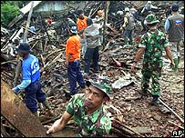 Indonesia soldiers and rescuers search through debris at Cijeruk village for survivors after tons of mud loosened by monsoon rains buried the village in Banjarnegara district, Central Java, Thursday,