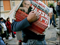 A newspaper seller holds copies of papers with the Hebrew headline: Struggles for his life