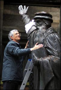 Rev Alan Greig puts a Make Poverty History band on the statue of John Knox