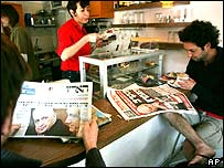 Israelis read the morning papers at a Tel Aviv coffee shop