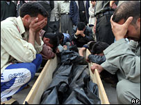 Relatives grieve over the coffin holding a victim in a suicide bomb attack outside of the hospital in Karbala