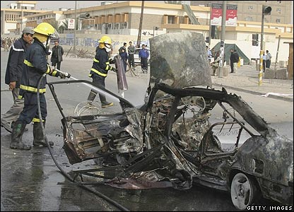 Firefighters douse the wreckage of a car bomb in Baghdad