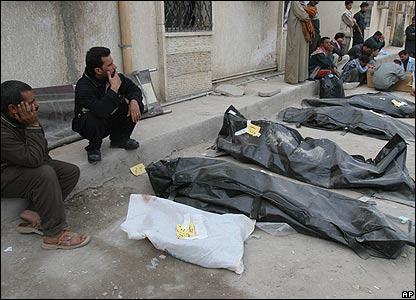 Relatives sit beside bodybags in Karbala