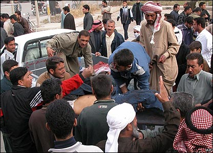 People carry wounded victims from the scene of a suicide bombing in Ramadi