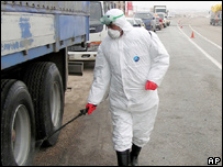 A Turkish health ministry official disinfects a lorry near the Turkish-Iran border