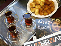 Tea and sweets next to Persian language magazines