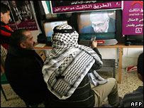 Palestinian shopkeepers watch the news about Ariel Sharon's health