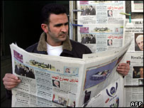 A Palestinian reads the news about Ariel Sharon's health
