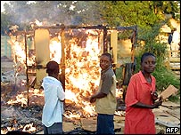 A stall burns after being set on fire by the police in the Harare suburb of Glen View