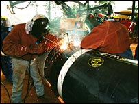 Welders working on Chad oil pipeline