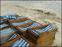 Deckchairs on windswept beach