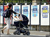 """A woman walks past campaign posters calling to vote """"No"""" in Caen"""