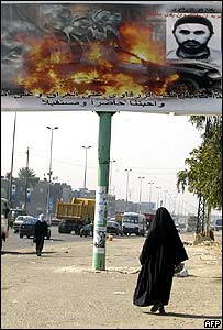A woman walks under an anti-terror poster showing Abu Musab al-Zarqawi in Baghdad (file picture)