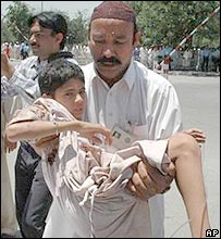 A hospital staff carries a boy injured in a suicide bombing