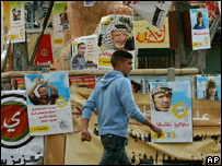 A Palestinian walks past election campaign posters in the West Bank city of Ramallah