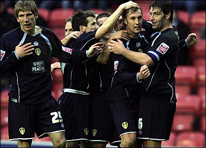 Rob Hulse (second right) is mobbed after scoring Leeds' equaliser at the JJB Stadium