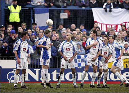 The Nuneaton defensive wall watches the ball sail into the top corner