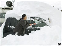 Japanese woman clears snow off her car in Tsunan, northern Japan