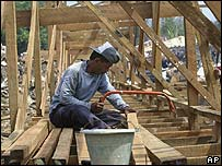 Worker building temporary barracks