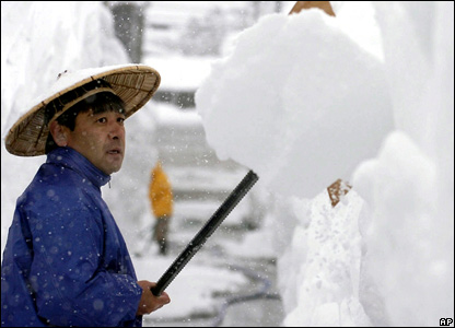 A man tries to clear a thick layer of snow from his house