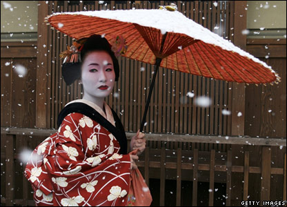 A geisha shelters beneath a parasol as snow falls in Kyoto, Japan