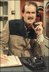 Actor John Cleese plays Basil Fawlty on the telephone in 1975