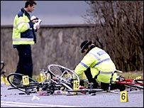 Police officers examine the fatal crash scene near Abergele
