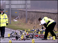 Police officers examine bicycle crash scene near Abergele