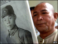 Man reading paper carrying photo of missing Japanese soldier who may be one of the two men
