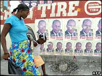 A woman walks past posters of a presidential candidate in Haiti
