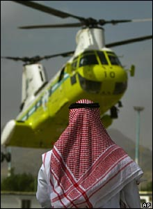 Man watching air ambulance helicopter land in Mecca