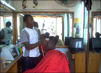 Peter having a hair cut at a barber in Kampala, Uganda