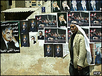 A Lebanese man walks past electoral posters of Saad Hariri and his father, in Beirut