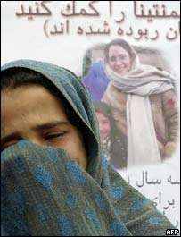 Child cries in front of poster with abducted Italian aid worker Clementina Cantoni