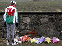 A cyclist wearing a Welsh cycling shirt stops to pay his respects