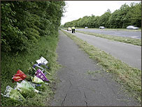 Flowers laid in tribute to the dead and injured by the side of the A4142