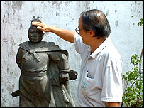 Touching Zheng He's statue for luck, Melaka