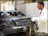 A man removes a uniform from the scene of a double suicide attack in the town of Hilla, Iraq