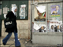 A Palestinian walks past election posters in East Jerusalem