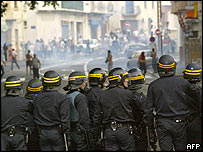 Riot police face members of the North African community in Perpignan on Sunday