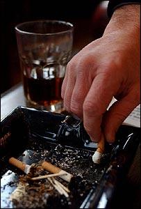Hombre apaga cigarrillo en un bar