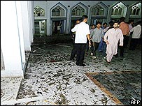 Pakistani Muslim devotees stand amongst the debris at a Shiite Muslim mosque following a bomb blast in Karachi