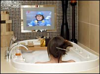 Woman watching wall-mounted screen in her bath
