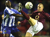 Wigan's Jason Roberts (left) tussles with Arsenal's Philippe Senderos