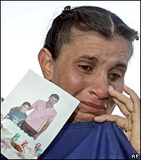 Mariela Conesa, holds a photograph of husband and son who were among the repatriated Cubans